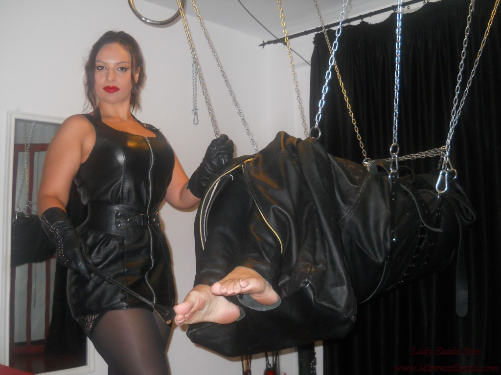 Mistress Ezada Sinn in leather torturing Her slave's feet
